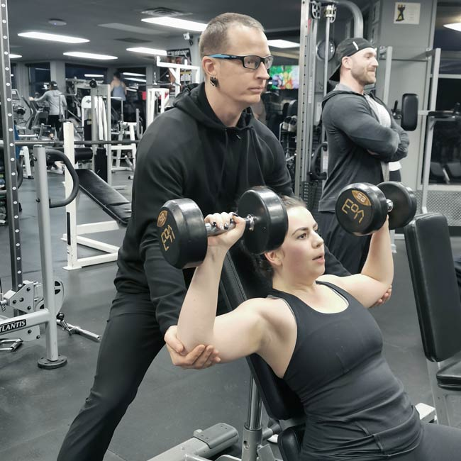 Coach Donovan training a personal training client in the gym with dumbbells